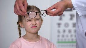 Opticien die correctief glazen verstoord meisje, de ziekten van het kinderjarenoog zetten stock footage