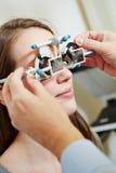 Opticien die proefglazen zetten Stock Afbeeldingen