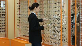 Opticien die showcase met glazen in opslag controleren stock video