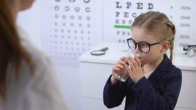 Opticien donnant des pilules à peu de fille, traitement de maladie oculaire, vitamines de vision banque de vidéos