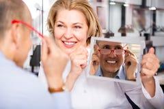 Opticien féminin consultant le client masculin mûr au sujet des cadres Photo libre de droits