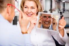 Opticien féminin de conseiller consultant le client masculin mûr au sujet des cadres Photo stock