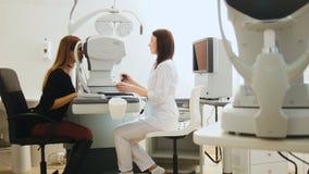 Opticien met tonometer en patiënt bij kenmerkende oogkliniek, royalty-vrije stock afbeeldingen