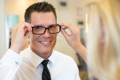 Opticien of optometrist die een klant over oogglazen raadplegen Stock Foto's