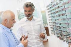 Optiker och man som väljer nya parexponeringsglas Arkivbilder
