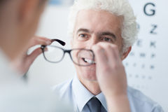 Optiker som ger nya exponeringsglas till patienten royaltyfri foto