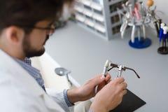 Optiker som reparerar och fixar ögonexponeringsglas Royaltyfri Bild