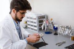 Optiker som reparerar och fixar ögonexponeringsglas Royaltyfri Fotografi