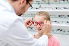 Optiker som sätter exponeringsglas till flickan på optiklagret royaltyfri foto