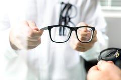 Optiker som visar nya exponeringsglas till kunden för att försöka royaltyfri bild