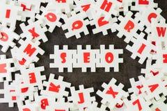 Optimisation de moteur de recherche, concept de SEO, puzzle blanc de puzzle avec l'alphabet établissant le mot SEO au centre du t photo stock