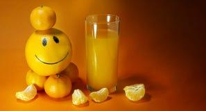 Optimism är ett sunt bantar ett orange lynne exponeringsglas av tangerinapelsinen för orange fruktsaft målade den smiley framsida arkivfoto