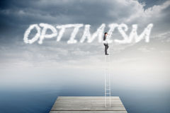 Optimism against cloudy sky over ocean. The word optimism and businessman standing on ladder using binoculars against cloudy sky over ocean Royalty Free Stock Photos