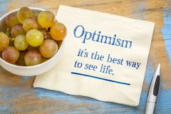 Optimism - best way to see life. Inspirational handwriting on a napkin with fresh grapes Stock Image