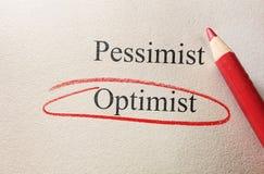 Optimism circle. Red pencil circle around Optimism, vs Pessimism stock image