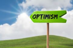 Optimism arrow sign. Optimism green wooden arrow sign on green land with clouds and sunshine royalty free stock images