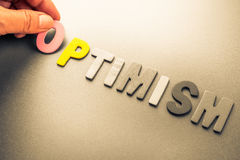 Optimism. Hand arrange wood letters as Optimism word Stock Images