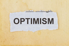Optimism. Newspaper cutout in an old paper background Stock Image