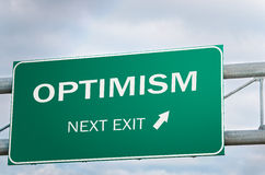 Optimism Next Exit, Creative Sign. Optimism Next Exit, Creative Highway Sign against Cloudy Sky Stock Photo