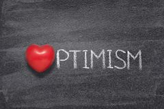 Optimism word heart. Optimism word handwritten on chalkboard with red heart symbol instead of O Stock Photo