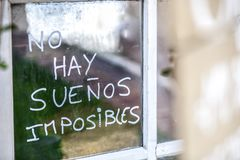 Optimist phrase written over old windows glasses in spanish Royalty Free Stock Photography