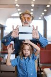 Optimistic aged gentleman is waiting for flight with child. Towards adventure. Portrait of joyful gray-haired grandfather is standing with his granddaughter Royalty Free Stock Image