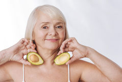 Optimistic aged woman having avocado halves in her hands. I love fruits. Optimistic nice aged woman holding avocado halves and putting them to her neck while Stock Images