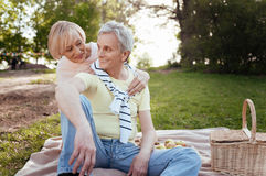 Optimistic aging couple sharing positivity at the picnic. Promise to love you forever . Happy lovely elderly couple expressing joy while hugging and enjoying royalty free stock photos