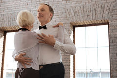 Optimistic aging dance couple enjoying waltz in the dance studio. Enjoying new hobby together. Talented smiling positive aging dance couple waltzing in the dance royalty free stock photos