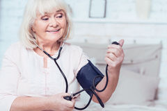 Optimistic aging woman checking blood pressure at home. Controlling my health. Smiling charming aged woman sitting on the bed at home and measuring blood royalty free stock image