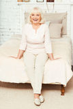 Optimistic aging woman expressing happiness at home. Enjoying every seconds of my life. Delightful smiling aging woman sitting on the bed at home while stock images