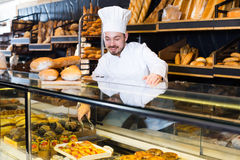 Optimistic baker showing assortment of bakery Royalty Free Stock Images