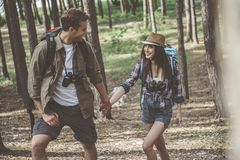 Optimistic boyfriend and girlfriend tourists are walking in pinewood royalty free stock photos