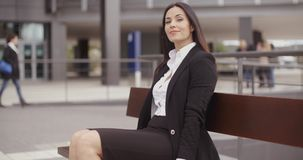 Optimistic business woman sitting outdoors stock video footage