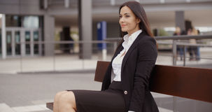 Optimistic business woman sitting outdoors Royalty Free Stock Image