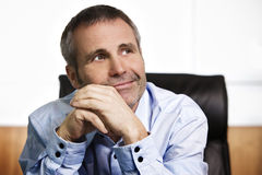 Optimistic businessman contemplating in office. Close up portrait of smiling business manager in blue shirt sitting in office looking up and resting chin on stock images