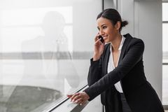 Optimistic charming lady is having phone conversation. Involved in communication. Cheerful elegant gorgeous businesswoman is standing in office while leaning on stock photo