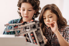 Optimistic children programming robot in the science studio. Studying science subject. Positive thoughtful concentrated children sitting in the science studio stock photo