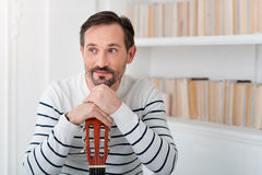 Optimistic dreamy man leaning on the guitar Royalty Free Stock Images