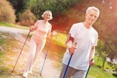 Optimistic elderly family walking with crutches in fresh air stock images