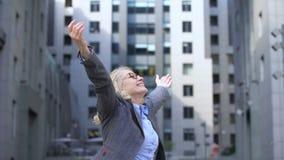 Optimistic elderly female turning around raising hands, enjoying life, vitality