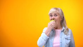 Optimistic elderly lady biting fresh green apple, healthy teeth, stomatology. Stock photo stock image