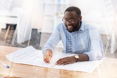 Optimistic engineer drawing a sketch at the table Stock Image