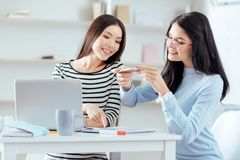 Optimistic female colleagues taking photo of documentation. Prospective business plan. Positive cheerful female colleagues smiling  while looking at the phone Stock Image