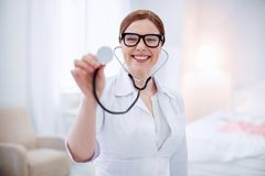 Optimistic female doctor demonstrating stethoscope stock photography