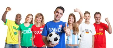 Optimistic french soccer fan with ball and fans from other count royalty free stock photo