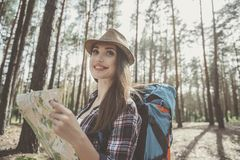 Optimistic girl hiker is traveling in pinewood royalty free stock images