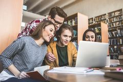Glad ladies and males using gadget. Optimistic girls and positive men working with laptop while sitting at table in library Royalty Free Stock Photography