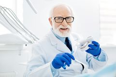 Optimistic glance of skilled dentist with false teeth. Reminding about healthcare. Close up of optimistic dentist with glasses holding false teeth and tooth Stock Photo