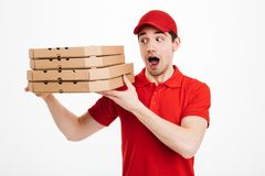 Optimistic guy dealer in red t-shirt and cap working in delivery. Service and holding stack of pizza boxes  over white background Royalty Free Stock Image